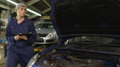 Female mechanic using a digital tablet for car diagnostics  Stock Footage