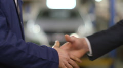 Close Up shot of mechanic and customer shaking hands in an auto repair shop Stock Footage