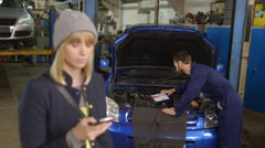 Happy customer on phone while a mechanic works on a car in the background Stock Footage