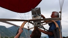 Hot air balloon pilot lighting the flame on his balloon - stock footage