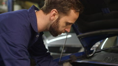 Mechanic using a digital tablet while doing routine maintenance on a car Stock Footage