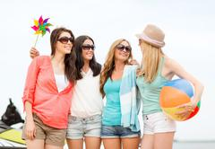 Stock Photo of smiling girls in shades having fun on the beach