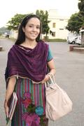 Attractive Indian female teacher walking on road. - stock photo