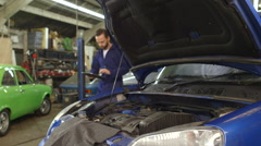 Mechanic using a digital tablet for a routine maintenance check-up on a car Stock Footage