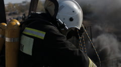 Firefighters in a gas mask doing their job standing high Stock Footage