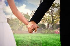 Composite image of mid section of newlywed couple holding hands in park - stock photo