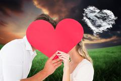 Composite image of attractive young couple kissing behind large heart Stock Illustration