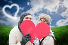 Composite image of attractive young couple in warm clothes holding red heart Stock Illustration