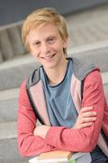 Smiling teenage student boy with books - stock photo