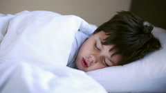 Little boy sleeping in bed, close up Stock Footage