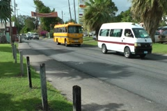 Caribbean Street Scene, Public service vehicles driving through Oistins - stock footage