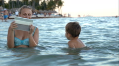 Mother with pad making photo or video of son in water Stock Footage