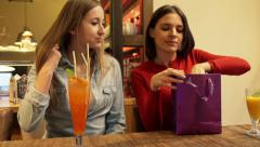 Woman showing just bought shirt to her friend in cafe HD - stock footage