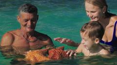 Man showing tourists two big starfish Stock Footage