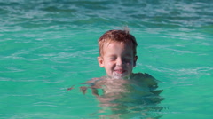 Little boy bathing in clear blue sea Stock Footage