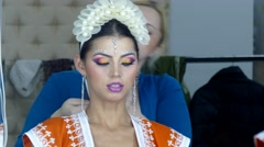 Make up artists making indian style make up to caucasian woman Stock Footage