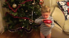 Child plays with toy near New Year tree Stock Footage