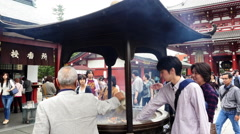 Worshipers Wave Incense Smoke for Good Luck -  Sensoji Temple  -  Tokyo Japan Stock Footage