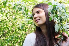 Young woman near apple tree - stock photo