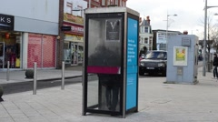 A Woman Uses a Telephone Booth to Make a Call Stock Footage