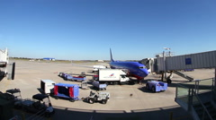 Wide angle of Southwest Airline plane at gate being serviced Stock Footage