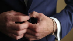 Groom buttoning his jacket. front view Stock Footage