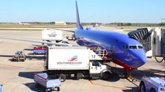 Closeup of Southwest airplane at gate with Food truck bed raising timelapse Stock Footage