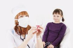 Doctor with syringe needle and girl scared of injections - stock photo