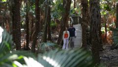 Couple walking along forest trail Stock Footage