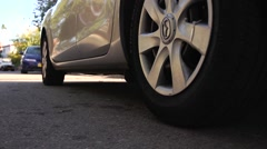 car driving away, close up of a car wheel - stock footage