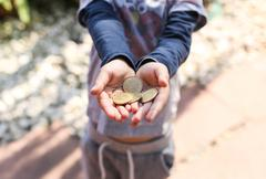 Child's Hand Holding Pretend Coins - stock photo