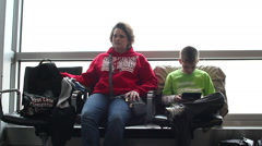 Mother and son waiting for flight at airport Stock Footage