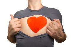 Man tearing apart grey t-shirt. Red heart painted on his chest isolated on wh - stock photo