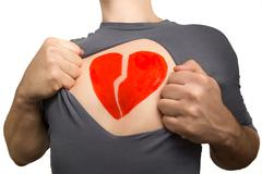 Man tearing apart grey t-shirt. Broken red heart painted on his chest isolate - stock photo