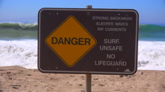 A sign along a California beach warns of dangerous surf and strong rip currents. Stock Footage