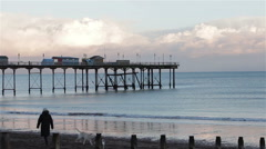 Sunset Over Teignmouth Pier - MS People Walking Dogs on Beach Stock Footage