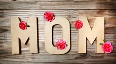 MOM text in big cardboard letters with flowers Stock Photos