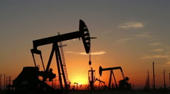 Footage - Oil Pumps Working Contineously  at Sunrise Stock Footage