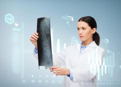 Serious female doctor looking at x-ray Stock Photos