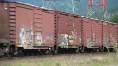 Railroad, freight train mixed long shot oblique angle. with power pylons in bg Stock Footage