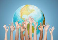 Human hands showing ok sign over earth globe Stock Photos