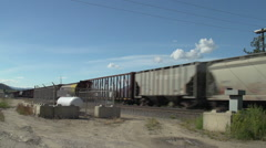 Railroad, freight train mixed wide shot with propane tank in fg Stock Footage