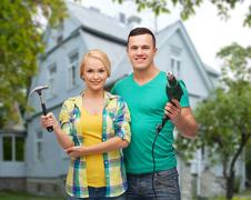 Smiling couple with hammer and drill over house Kuvituskuvat