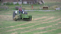 Agriculture, tractor baling long shot, older farmer Stock Footage