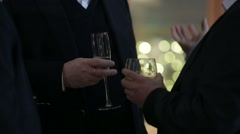 Man in black suit hold glass with champagne and drinks it, closeup Stock Footage