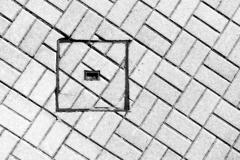 Abstraction of sewer manhole on floor with cobblestones Stock Photos