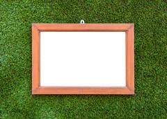 Empty Wooden photo frame hang on Artificial Green grass background Stock Photos