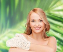 smiling woman with exfoliation glove - stock photo