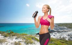 Sporty woman drinking water from sportsman bottle Stock Photos