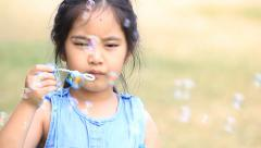 Little Asian child having fun making bubbles - stock footage